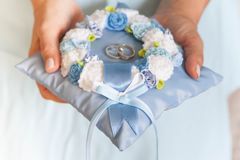 Golden wedding rings on small blue and Turquoise cushion. Golden wedding rings on small blue Royalty Free Stock Photos