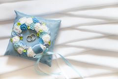Golden wedding rings on small blue and Turquoise cushion. Golden wedding rings on small blue Stock Images