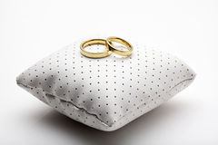 Golden wedding rings on small cushion. Golden wedding rings on small white leather cushion stock images