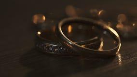 Golden wedding rings on the table. Light illuminated background stock video