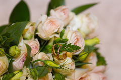 Golden wedding rings on wedding bouquet of pink roses. Golden wedding rings with small diamonds on wedding bouquet of tiny pink roses for bride and groom Stock Images