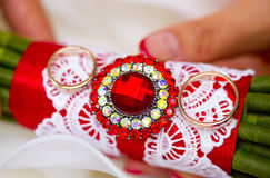 Golden wedding rings on wedding bouquet with red ribbon and brooch. Golden plain wedding rings on wedding bouquet with red ribbon, white lace and brooch Stock Image