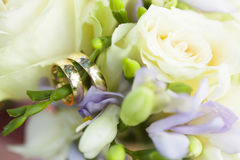 Golden wedding rings on wedding bouquet of white roses and violet flowers Stock Image