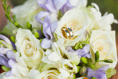 Golden wedding rings on wedding bouquet of white and violet flowers. Golden wedding rings on wedding bouquet of white roses and violet flowers with green buds Stock Photography