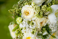 Golden wedding rings on wedding bouquet of yellow flowers. White roses, lilac and ears of wheat Stock Images
