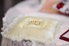 Golden wedding rings on white ring bearer pillow Royalty Free Stock Photos