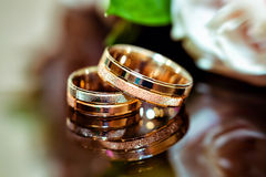 Golden wedding rings and white roses.  Royalty Free Stock Images
