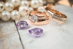 Golden wedding rings on white wood background Stock Photos