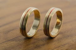 Golden wedding rings on wooden surface Royalty Free Stock Image