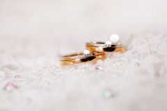 Golden wedding ringswith diamonds lie on lace silk fabric. Royalty Free Stock Photography