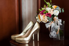 Golden wedding shoes and gentle bridal bouquet with lace bow Stock Photo