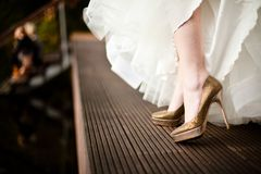 Golden wedding shoes from white dressed bride stock photography