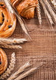 Golden wheat ears raisin rolls croissant on oaken. Wooden board food and drink concept Royalty Free Stock Photos