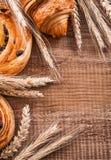 Golden wheat ears raisin rolls croissant on oaken Royalty Free Stock Photos