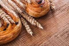 Golden wheat ears tasty raisin pastry on oaken. Wooden board food and drink concept Stock Photo