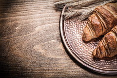 Golden wheat rye ears fresh croissants copper tray on vintage wo Royalty Free Stock Image