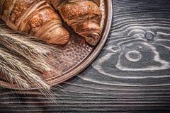 Golden wheat rye ears tasty rolls brass tray on wood board food Royalty Free Stock Photo