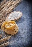 Golden wheat rye ears wooden spoon flour uncooked pasta on black Stock Photos