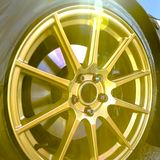 Golden wheel rim of a car on a bright sunny day. Customized wheel rim of a car with disc brake seen between the golden spokes. Bright sunlight reflects on the stock photos