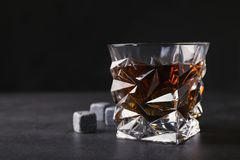 Golden whiskey in glass with cooling stones on table. stock images