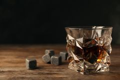 Golden whiskey in glass with cooling stones on table. royalty free stock image