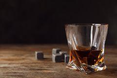 Golden whiskey in glass with cooling stones on table. royalty free stock photos