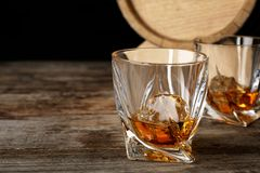 Golden whiskey in glass with ice cube. On wooden table royalty free stock image