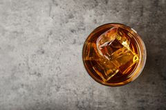 Golden whiskey in glass with ice cubes on table stock images