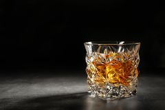Golden whiskey in glass with ice cubes on table. stock images