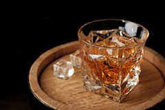 Golden whiskey in glass with ice cubes on wooden barrel. Space for text stock photos
