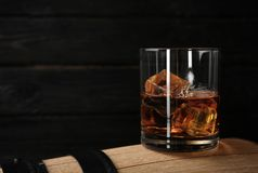 Golden whiskey in glass with ice cubes on wooden barrel. Space for text stock images