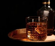 Golden whiskey in glass with ice cubes on wooden barrel. Space for text stock image