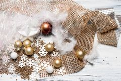 Golden and white christmas decoration on white wooden background, stock photography