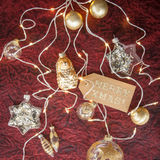 Golden and white christmas ornaments. Golden and white glass ornaments for christmas on dark red background royalty free stock image