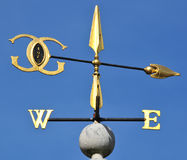 Golden wind vane. Against a clear blue sky stock image