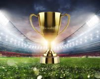 Golden winner s cup in the middle of a soccer stadium with audience. Concept of triumph in a football final match in a stadium stock photo