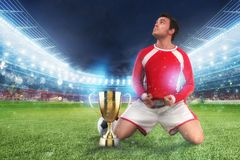 Golden winner`s cup in the middle of a stadium with audience. Player on his knees raises a fist to the sky to celebrate the win royalty free stock image