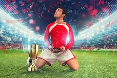 Golden winner`s cup in the middle of a stadium with audience. Player on his knees raises a fist to the sky to celebrate the win stock photography