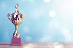 Golden winner`s trophy on sky background standing on wooden desk festive bokeh blur background. S stock images