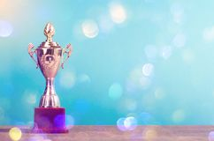 Golden winner`s trophy on sky background standing on wooden desk festive bokeh blur backgrounds. Golden winner`s trophy on sky background standing on wooden desk stock photography
