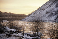 Golden winter river. Flowing through the hills at sunset Royalty Free Stock Image