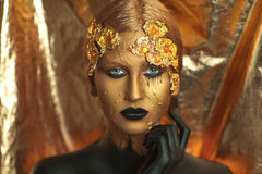 Golden woman. Magic golden girl with bright makeup. Streams of gold, shiny tears drops on the cheeks, black hand in the paint for body art. Big lips, long Stock Image
