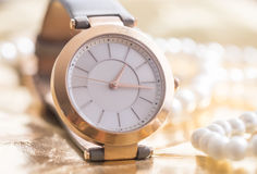 Golden woman watch. Golden wrist watch, golden woman watch concept with white pearls Royalty Free Stock Photo