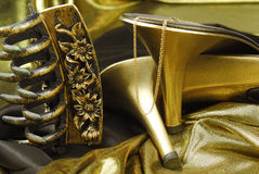 Golden womans shoes. The golden womans shoes  with hairgrip and golden jewelry on golden background Stock Images
