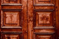 Old wooden door on a wooden and glass door. Golden wooden door on a wooden and glass door with scratches stock image