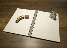 Golden wooden train and stone house on blank white notebook. On wooden table stock images