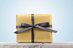 Golden wrapped gift box with black ribbon Royalty Free Stock Photo