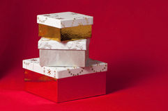Golden wrapped presents. Stack of gifts in boxes on red cloth background waiting for christmas royalty free stock image