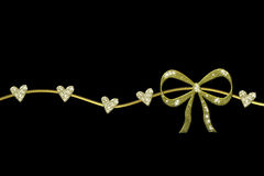 Golden wreath with gift bow and glossy hearts Stock Photos