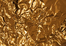 Golden wrinkled foil texture for background Stock Images